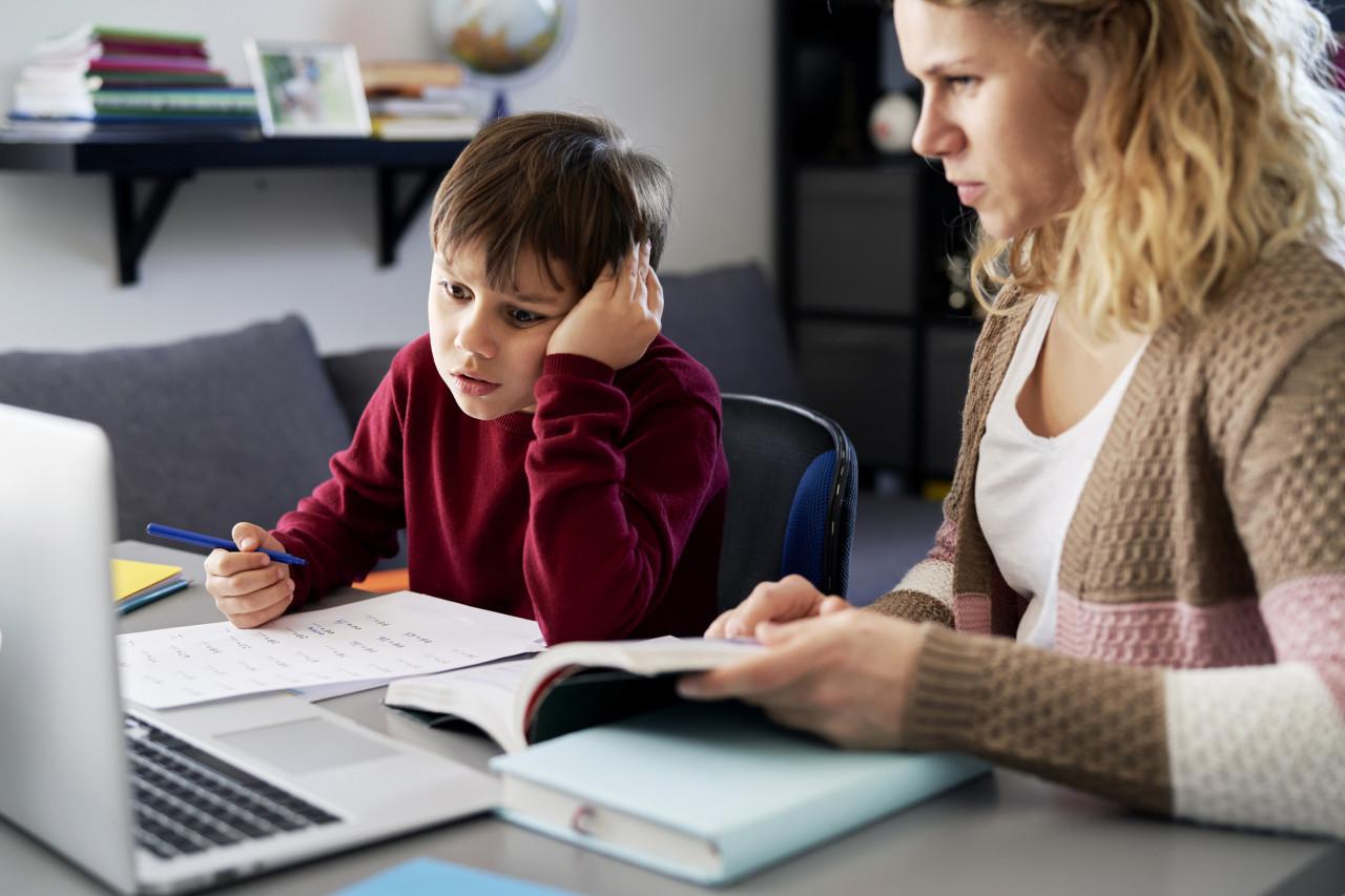Mère aidant sont enfant dans ses travaux d'école à la maison