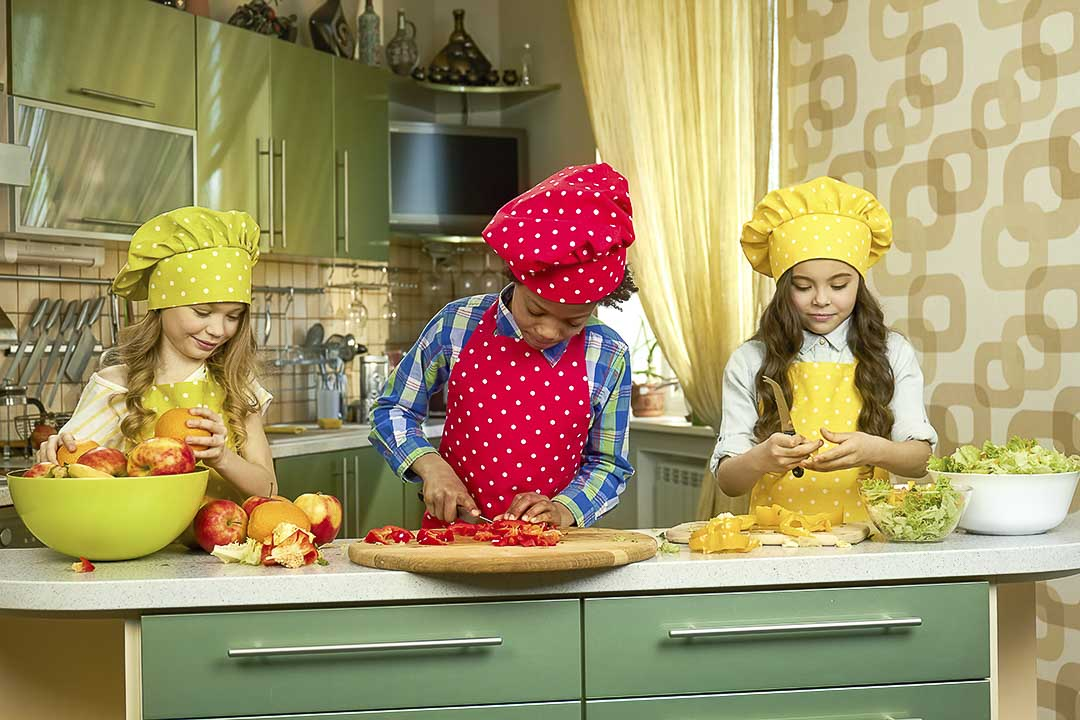 Three children learning to cook