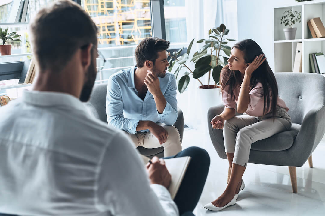 Couple argues in therapy session as psychologist analyzes their situation